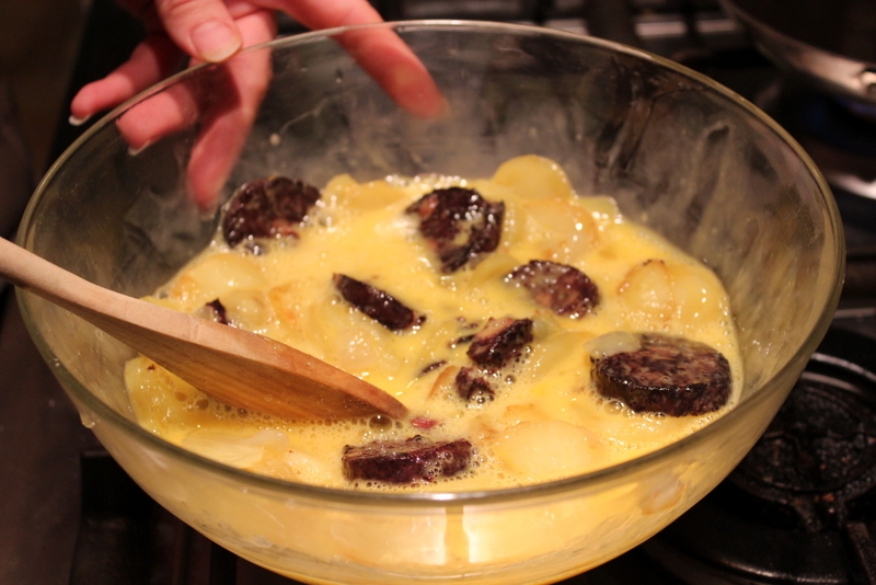 Mixing eggs, potatoes & black pudding for tortilla